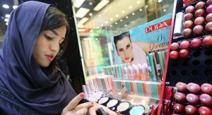 An Iranian woman checks make up at a cosmetics shop in northern Tehran on May 6, 2014. (photo credit: AFP/Atta Kenare)